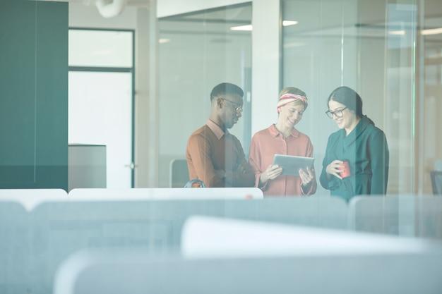 Cintura para cima retrato de três executivos sorridentes discutindo trabalho em pé atrás de uma parede de vidro no escritório