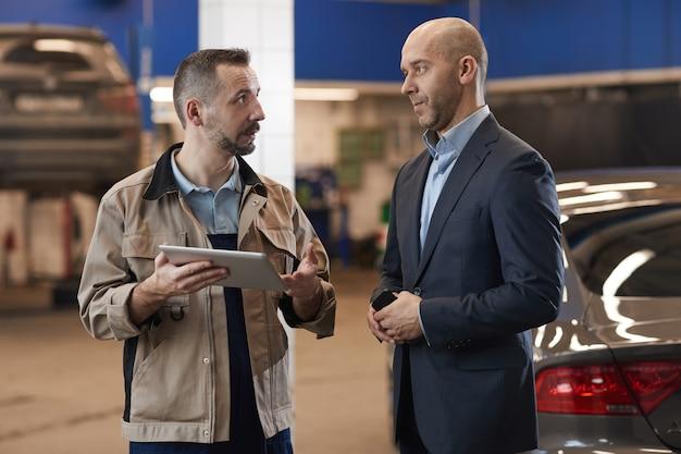 Cintura para cima, retrato de um empresário maduro falando com um mecânico enquanto verifica um carro de luxo na inspeção anual