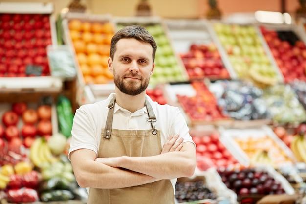 Cintura para cima, retrato de um homem barbudo olhando em pé ao lado de uma barraca de frutas e legumes no mercado