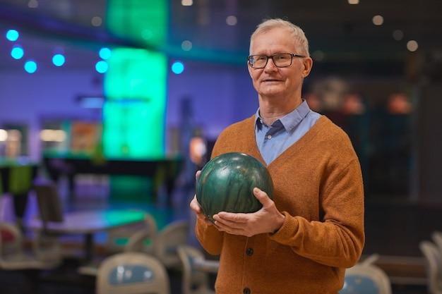 Cintura para cima, retrato de um homem sorridente sênior segurando uma bola de boliche e olhando para a câmera enquanto desfruta de entretenimento ativo na pista de boliche, copie o espaço