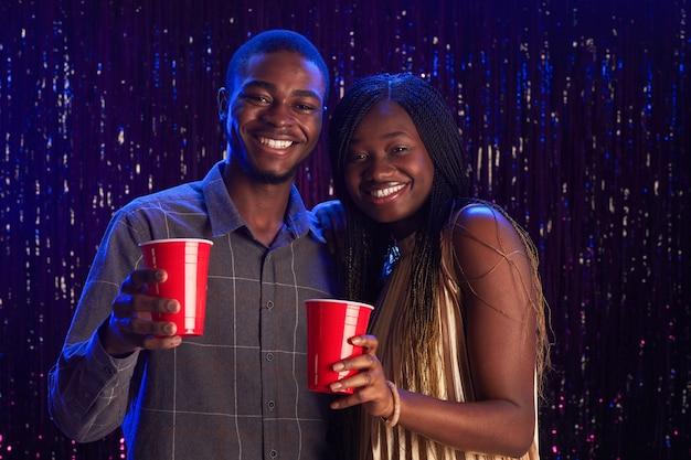Cintura para cima retrato de um jovem casal afro-americano segurando copos plásticos vermelhos e sorrindo para a câmera enquanto aproveita a festa