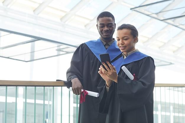 Cintura para cima, retrato de um jovem casal afro-americano usando vestidos de formatura enquanto tira uma selfie dentro de casa no interior moderno da universidade, copie o espaço