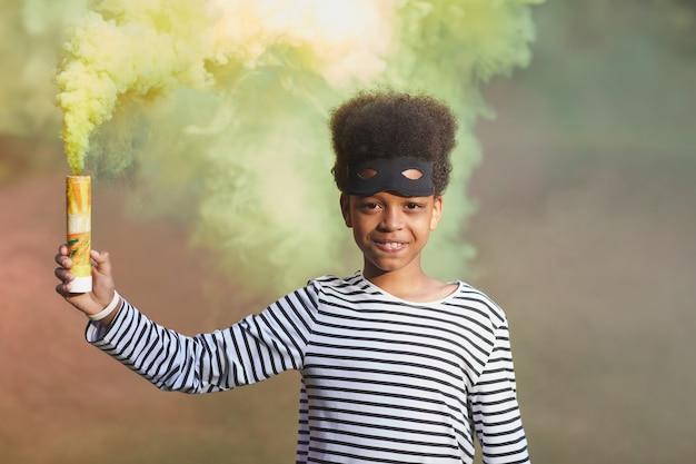 Cintura para cima, retrato de um sorridente menino afro-americano vestindo fantasia de halloween e segurando uma fumaça verde, copie o espaço