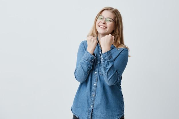 Cintura para cima retrato de uma deliciosa garota feliz sorridente com óculos, vestido com camisa jeans, fecha os punhos, se alegra boas notícias, estar confiante em seu grande sucesso. eu consegui!