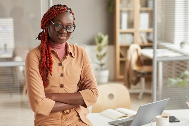 Cintura para cima retrato de uma jovem afro-americana sorrindo para a câmera enquanto se inclina na mesa no interior de um escritório moderno, copie o espaço
