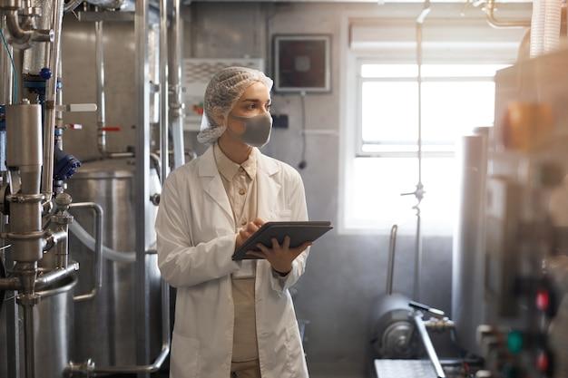 Cintura para cima retrato de uma jovem usando máscara e segurando um tablet digital durante a inspeção de controle de qualidade em uma oficina iluminada pelo sol na fábrica de alimentos, copie o espaço