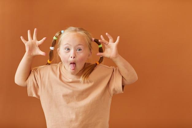 Cintura para cima, retrato de uma linda garota com síndrome de down fazendo caretas para a câmera em pé contra uma superfície marrom lisa no estúdio, copie o espaço