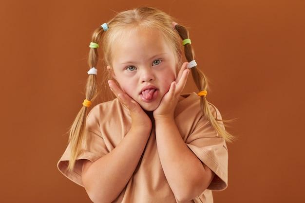 Cintura para cima, retrato de uma linda garota com síndrome de down fazendo uma careta para a câmera em pé contra uma superfície marrom lisa no estúdio, copie o espaço