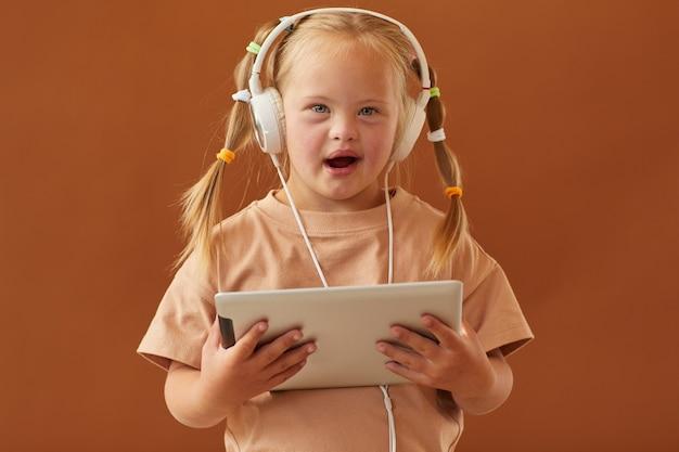 Cintura para cima, retrato de uma linda garota com síndrome de down segurando um tablet digital e em pé contra uma superfície marrom lisa no estúdio, copie o espaço