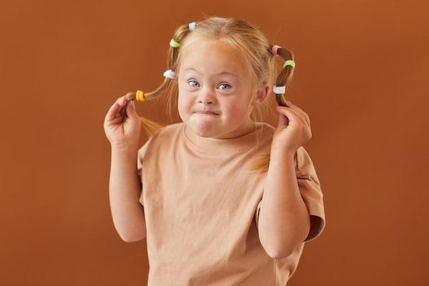 Cintura para cima, retrato de uma linda garota loira com síndrome de down fazendo caretas para a câmera em pé contra uma superfície marrom lisa no estúdio, copie o espaço