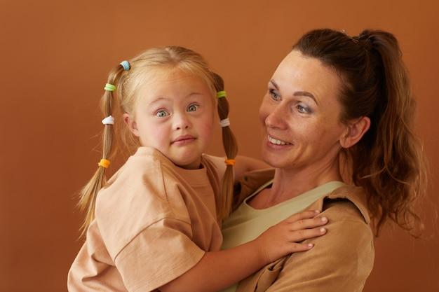 Cintura para cima, retrato de uma mãe feliz e madura segurando a filha com síndrome de downs, em pé contra uma superfície marrom lisa em um estúdio