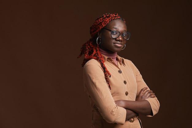 Cintura para cima, retrato de uma mulher afro-americana confiante olhando para a câmera enquanto posa em pé com os braços cruzados contra um fundo marrom escuro em estúdio, copie o espaço