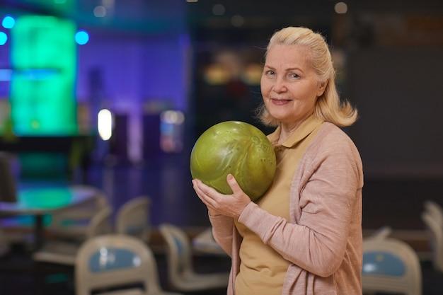 Cintura para cima, retrato de uma mulher elegante sênior segurando uma bola de boliche e sorrindo para a câmera enquanto desfruta de entretenimento ativo na pista de boliche, copie o espaço