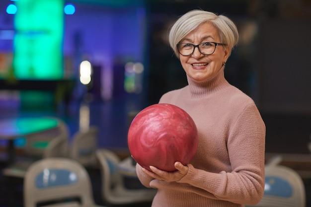 Cintura para cima, retrato de uma mulher sorridente sênior segurando uma bola de boliche e olhando para a câmera enquanto desfruta de entretenimento ativo na pista de boliche, copie o espaço
