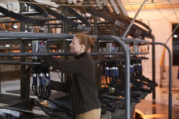Cintura para cima, retrato de uma trabalhadora configurando uma máquina de ordenha de vacas em uma moderna fazenda de laticínios, copie o espaço