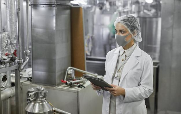 Cintura para cima, retrato de uma trabalhadora usando máscara e segurando um tablet digital durante a inspeção de controle de qualidade na fábrica de alimentos, copie o espaço