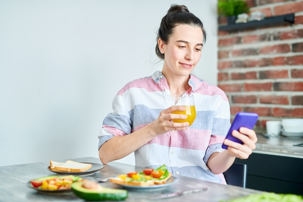 Cintura para cima retrato pf sorridente jovem desfrutando café da manhã em casa e verificar as mídias sociais, cópia espaço