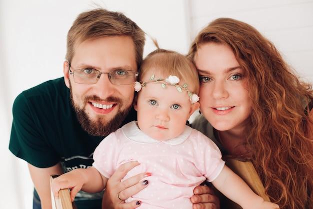 Cintura para cima sorrindo jovem pai e mãe abraçando seu bebê recém-nascido enquanto posavam para a câmera. conceito de paternidade