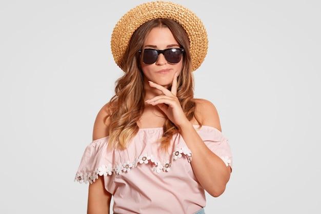 Cintura para cima tiro da bela jovem caucasiana com expressão facial pensativa, mantém o dedo na bochecha, usa óculos de sol da moda