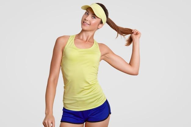 Cintura para cima tiro de auto-confiante bela tenista saudável detém rabo de cavalo, vestido com roupas esportivas, posa na parede branca do estúdio, repousa após jogo ativo ou competição. conceito de recreação