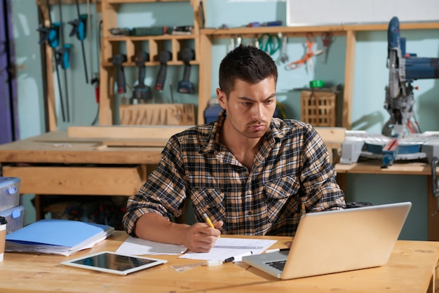 Cintura para cima tiro de carpinteiro bonito, planejando o trabalho no próximo projeto, olhando para o laptop com lápis na mão