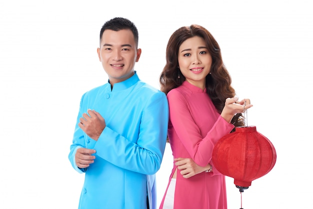 Cintura para cima tiro de casal em roupas tradicionais em pé ombro a ombro contra branco