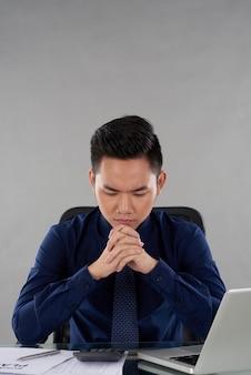 Cintura para cima tiro de executivo de negócios asiáticos sentado na mesa de escritório, pensando sobre o desempenho financeiro