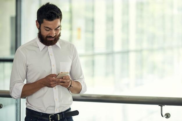 Cintura para cima tiro de homem de negócios na camisa branca usando seu smartphone em uma pausa