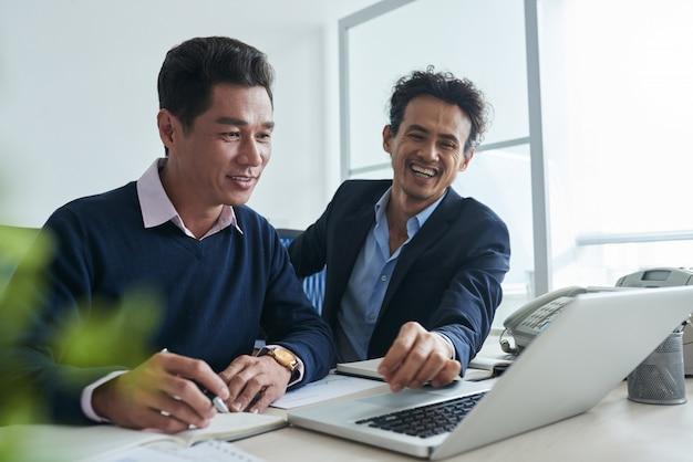 Cintura para cima tiro de homens de negócios, navegar na net no laptop togther