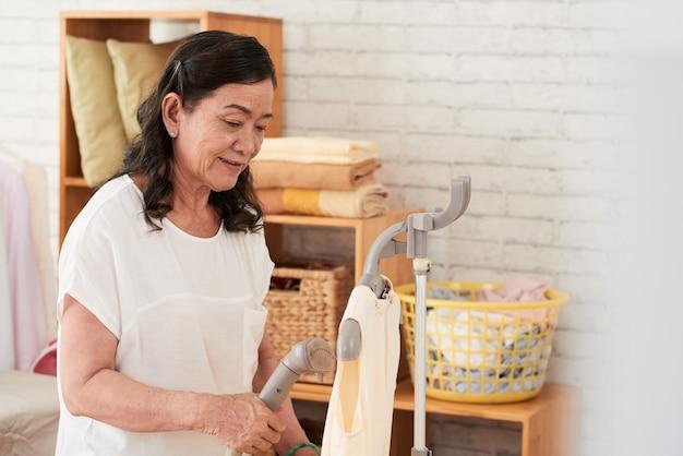 Cintura para cima tiro de mulher asiática cozinhando sua blusa de seda