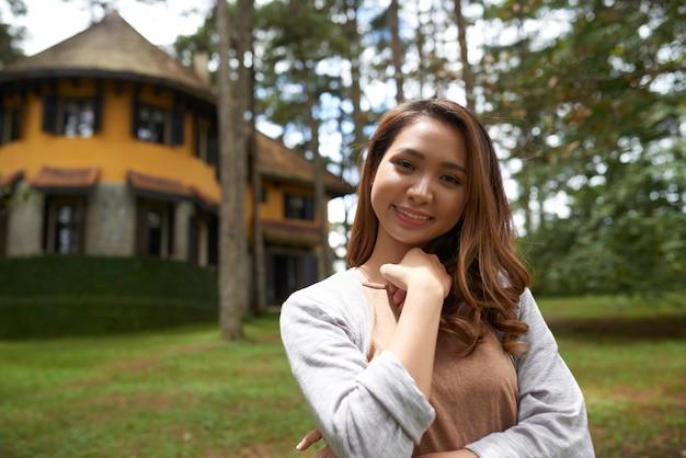 Cintura para cima tiro de mulher asiática em pé na frente de sua casa