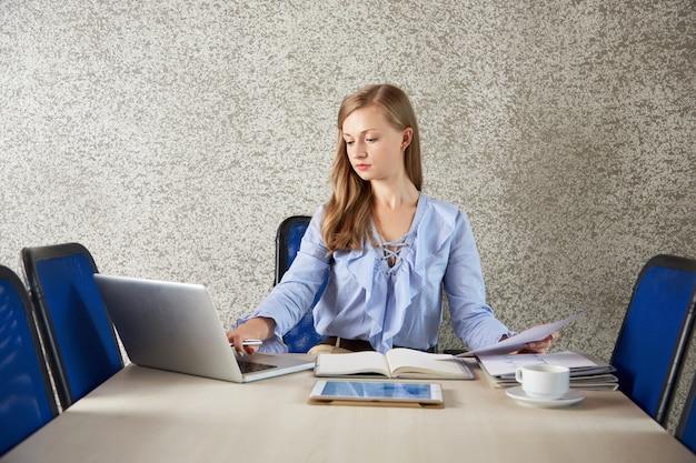 Cintura para cima tiro de mulher de negócios, sentado na mesa de escritório, trabalhando no laptop com papéis