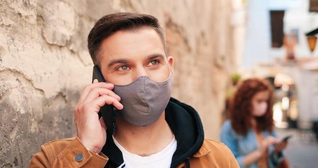 Cintura para cima, vista de retrato de um homem caucasiano moreno usando máscara protetora, tendo conversatio ...