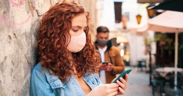 Cintura para cima, vista de retrato de uma garota ruiva caucasiana usando máscara protetora usando seu smartphon.