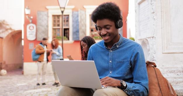 Cintura para cima, vista do retrato de um homem multirracial usando fones de ouvido, sentado na rua e tendo ...