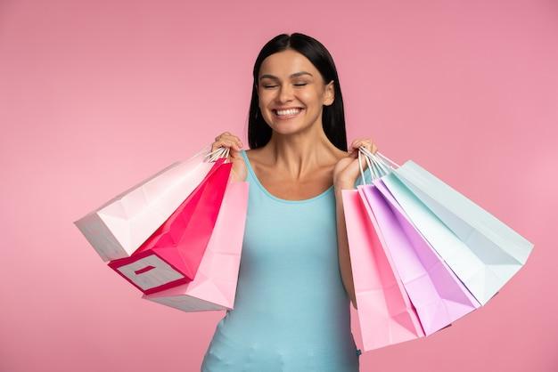 Cintura para cima, vista do tamanho do corpo dela, ela bonita, elegante, carregando mercadorias de coisas novas, isoladas em um fundo de cor rosa vibrante de brilho vívido brilhante