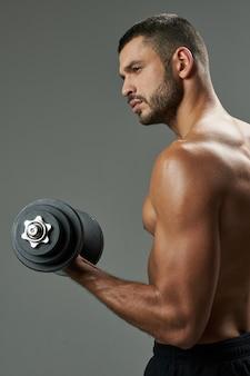 Cintura para cima, vista lateral, retrato de um atraente esportista caucasiano em roupas esportivas pretas, segurando um haltere na mão enquanto desvia o olhar dentro de casa