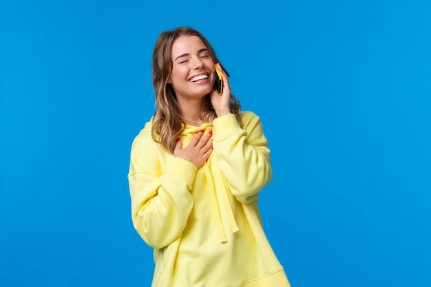 Cintura-se retrato de jovem sorridente alegre tendo conversa engraçada no telefone, segurando o smartphone perto da orelha, fechar os olhos e rindo como toque no peito, em pé em uma parede azul