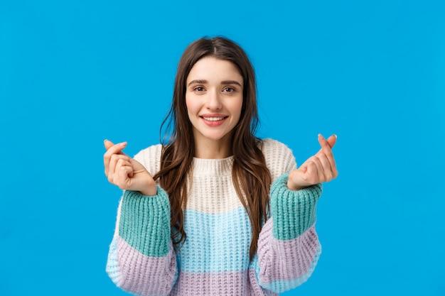 Cintura-se retrato linda garota adorável romântica, na camisola de inverno, sorrindo sentindo otimista, mostrando corações coreanos