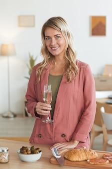Cintura vertical para cima retrato de mulher loira elegante sorrindo para a câmera e segurando uma taça de champanhe enquanto cozinha para jantar dentro de casa