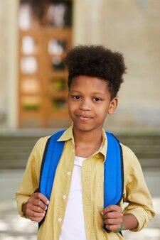 Cintura vertical para cima retrato de um estudante afro-americano carregando uma mochila e sorrindo para a câmera enquanto posa ao ar livre contra o prédio da escola