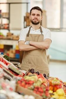 Cintura vertical para cima, retrato de um homem barbudo em pé com os braços cruzados, olhando enquanto vende frutas e vegetais frescos no mercado de fazendeiros