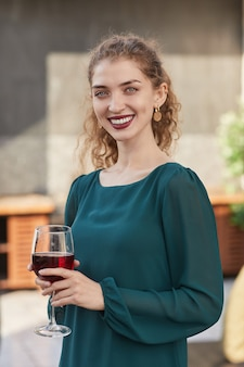 Cintura vertical para cima retrato de uma jovem sorridente segurando uma taça de vinho e enquanto aproveita a festa ao ar livre