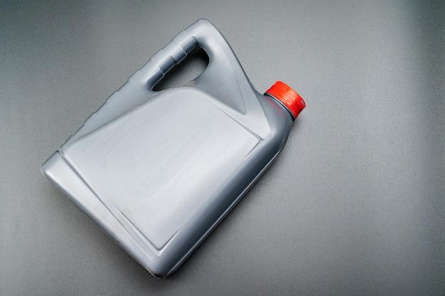 Cinza com uma lata de tampa vermelha com óleo de máquina em um fundo preto. óleos de motor para reduzir o atrito entre as peças móveis do motor. serviço e loja de automóveis