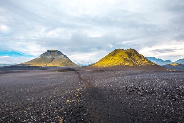 Cinzas vulcânicas e duas montanhas verdes. landmannalaugar, islândia