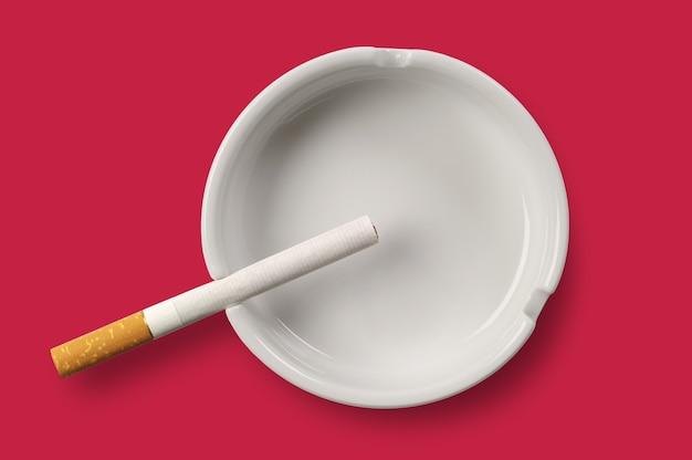 Cinzeiro branco e cigarro sobre fundo vermelho. vista do topo