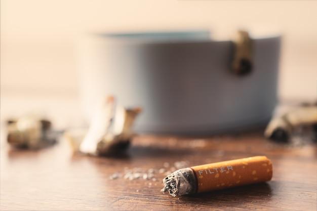 Cinzeiro com cigarro na mesa de madeira.