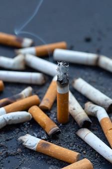 Cinzeiro e cigarros fumados em fundo escuro.
