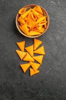 Cips de queijo laranja com pimenta picante na superfície escura, cor de milho e batata salgada