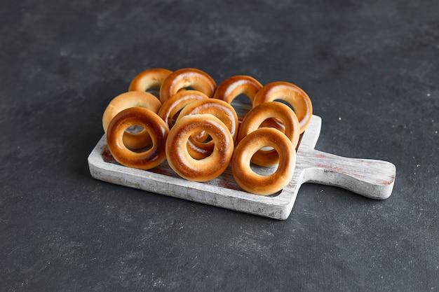 Circule os biscoitos em uma travessa de madeira branca sobre a mesa.